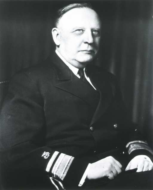 <p>Seated, naval uniform, rear-admiral, hands in lap.</p>