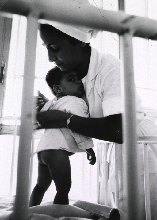 <p>A nurse is leaning over the side of a crib and is dressing a young child.</p>