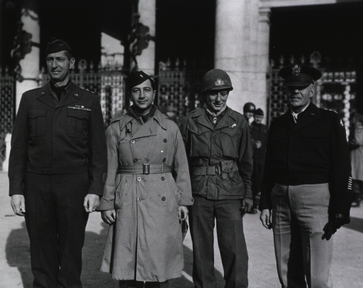 <p>The four men stand in a row facing the camera in daylight in front of an unidentified building.  Other servicemen stand in the background and watch.</p>