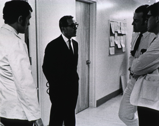 <p>Three quarter length, right pose, wearing glasses; standing in hallway of hospital (UCLA) with three students - on teaching rounds.</p>