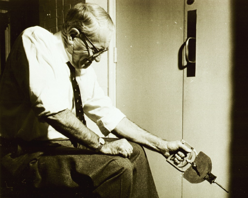 <p>An elderly man, with his shirt sleeves rolled up to his elbows, manipulates a hand dynameter with his right hand.</p>