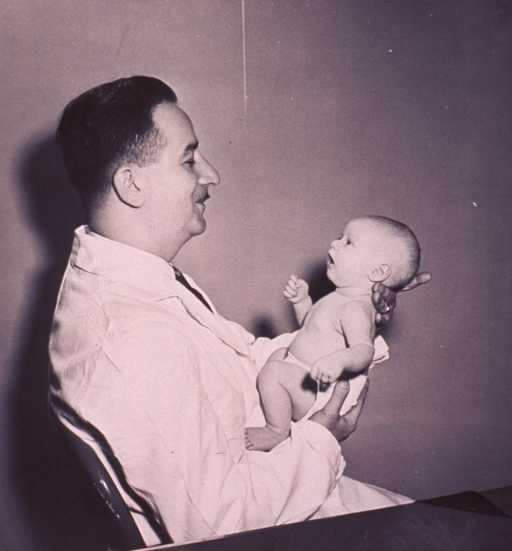 <p>A physician is holding an infant.</p>