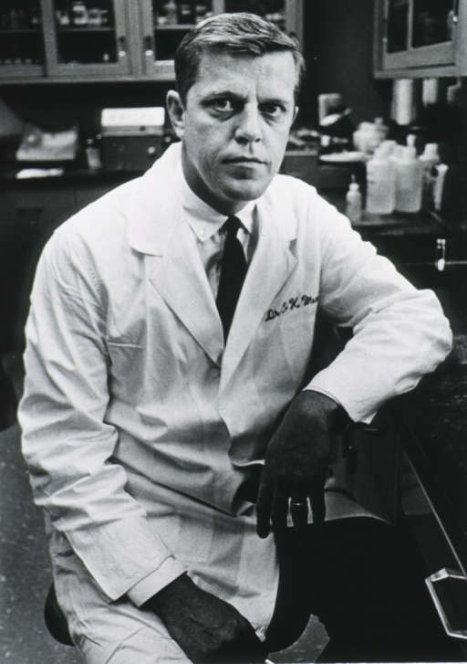 <p>Three quarter length, full face; wearing lab coat; seated in laboratory; left arm resting on lab desk.</p>