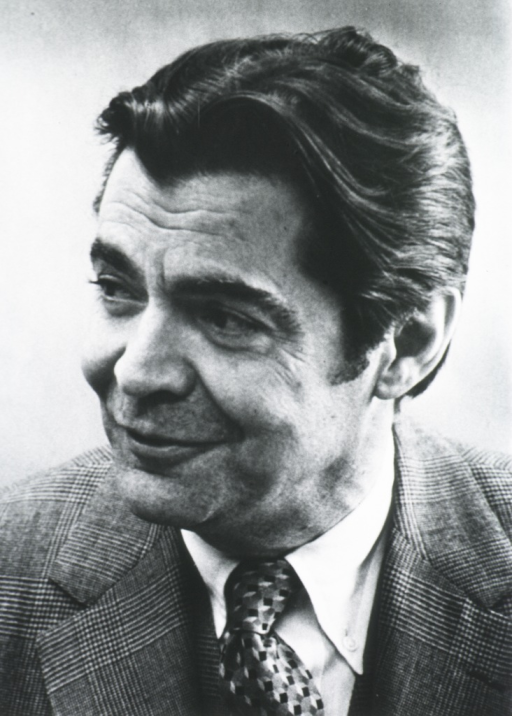 <p>Head and shoulders, face down and to the left, smiling, wearing plaid suit.</p>