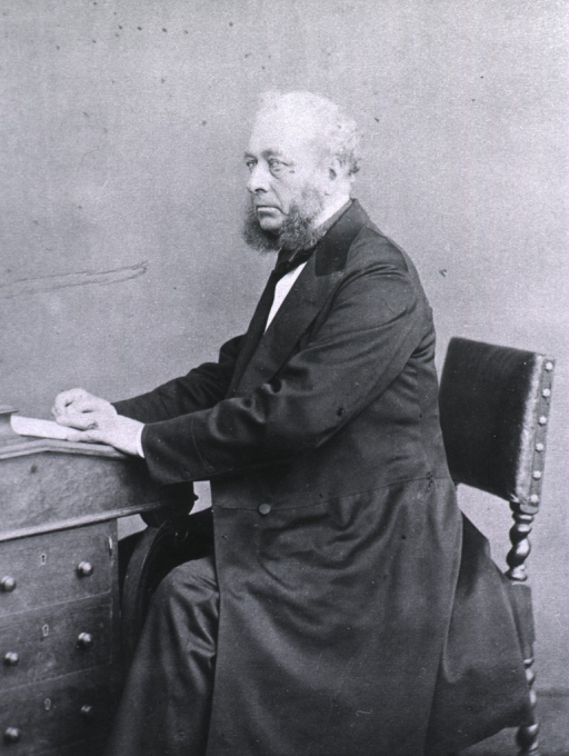 <p>Seated at a writing desk; left pose.</p>