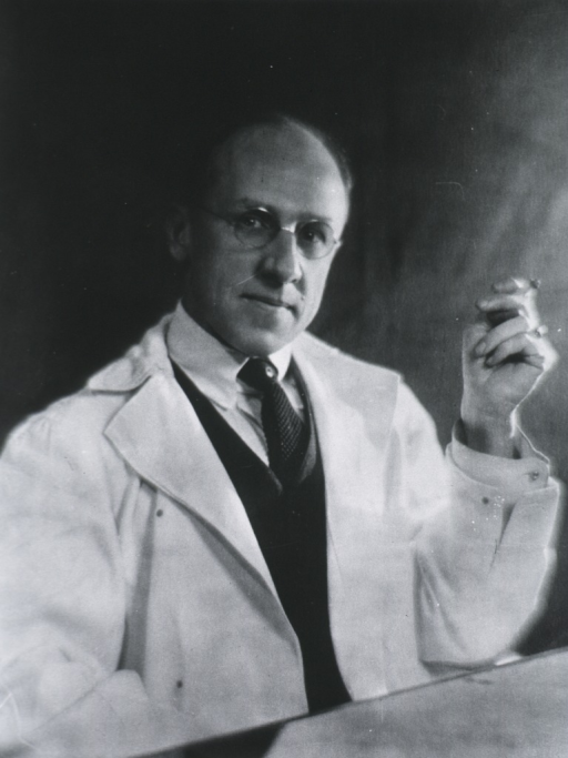 <p>Half-length, seated at table, right pose, full face; wearing white coat and glasses; holding cigarette.</p>