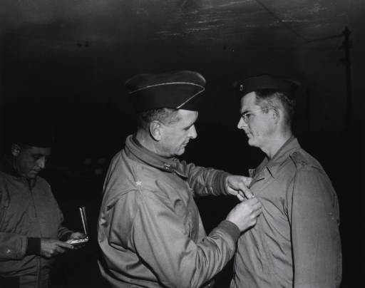 <p>Brig. General Martin pins the medal on the jacket of Major Mason while a third serviceman stands in the background holding the medal case.</p>