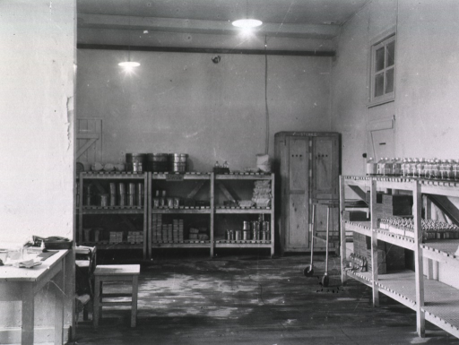 <p>Various supplies are placed on shelves in a room with a high ceiling.</p>