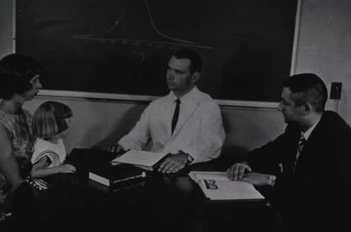<p>A woman with a child on her lap sits at a table with a physician and another man.</p>