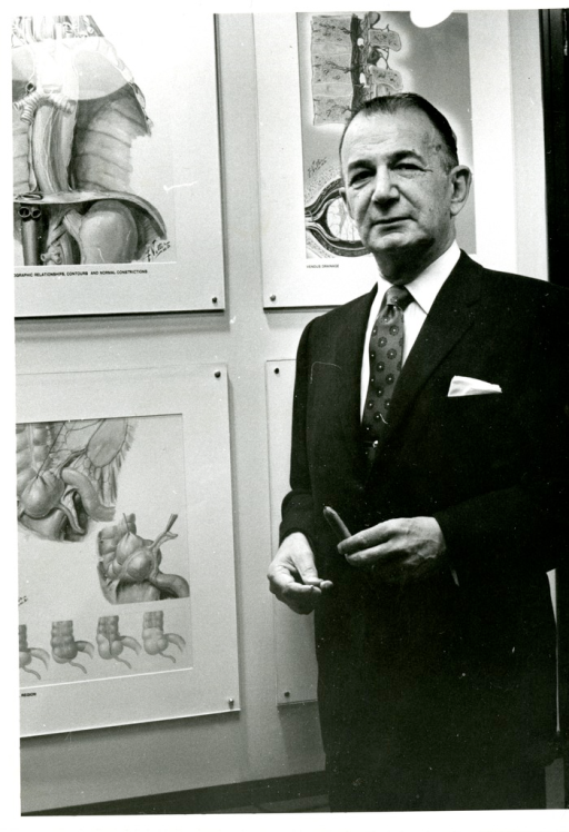 <p>Surgeon and medical illustrator Dr. Frank Henry Netter, MD, stands next to his displayed artwork.</p>