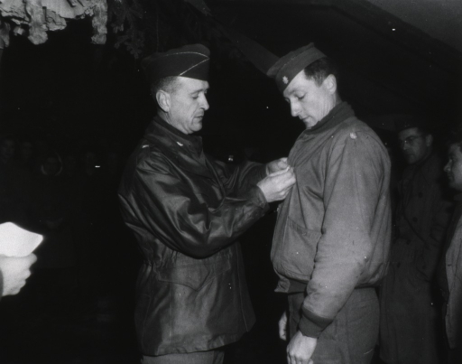 <p>Brig. General Martin pins the medal on the jacket of Lt. Col. Holmboe while a group of servicemen and women watch.</p>