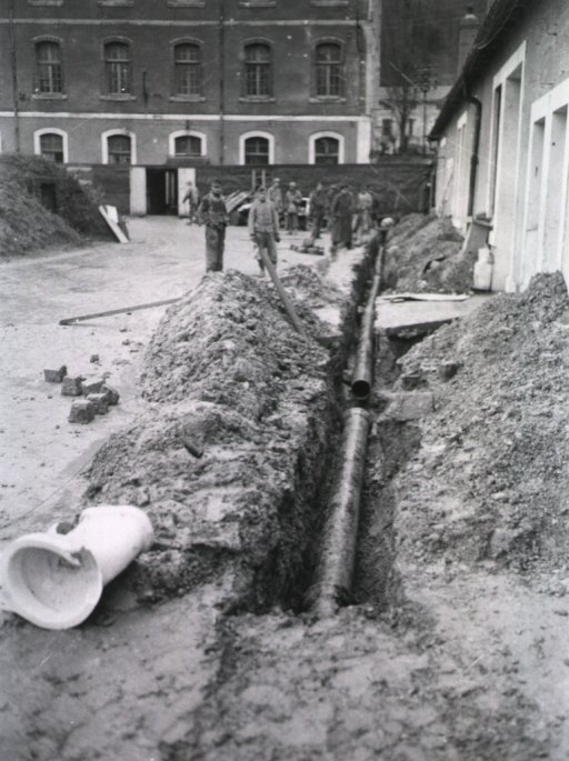 <p>Men stand next to a ditch in which several pipes are positioned.</p>