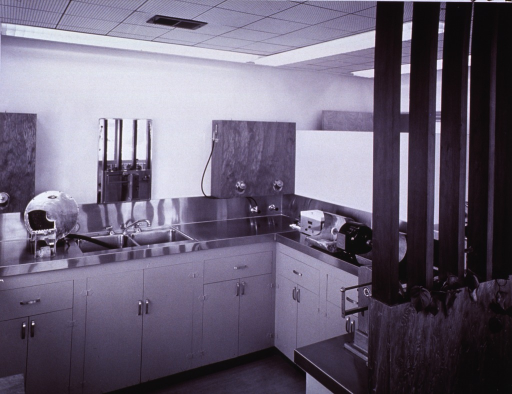 <p>Interior view of a partitioned area within a larger room: a double sink; on the counter is a grinder and other equipment.</p>