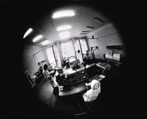 <p>Interior view: a nurse/technician is sitting at a monitoring station in the middle of the room, from here she monitors the electrocardiograms of the patients; at the far end of the room are three units occupied by patients.</p>