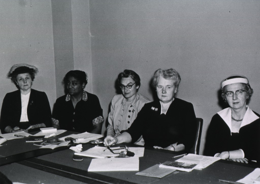 <p>View of five of the board members seated around a table.</p>