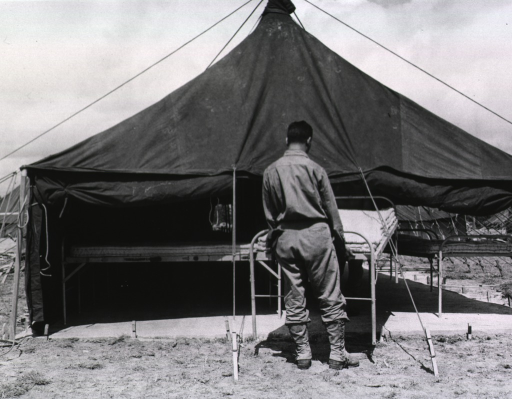 <p>A serviceman moves a single bed into a hospital tent.</p>