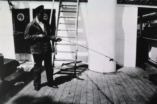 <p>View of a U.S. Public Health Service worker standing on the deck of a ship, facing right, holding a long pole at the end of which dangles a captured rat.</p>