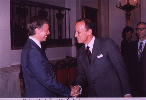 <p>Dr. Donald S. Fredrickson is visiting the White House.  He and President Jimmy Carter are shaking hands.  Dr. Arthur Upton, director of the National Cancer Institute, is standing behind Dr. Fredrickson.  In the background there is a red straight-backed chair-like sofa, a staircase with a landing and a decorative interior fence, and a picture on the wall.</p>