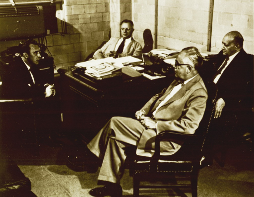 <p>Four men are seated around a desk in an office.</p>