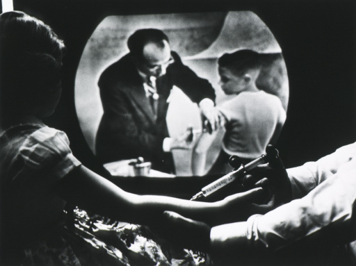 <p>Cheryl Halpin, (foreground) watches Dr. Salk on television, inoculating child with polio vaccine (part of a closed circuit television show from the Univ. of Michigan).</p>