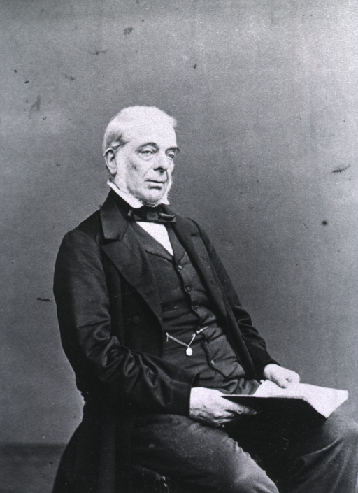 <p>Seated holding an open book on lap; right pose.</p>