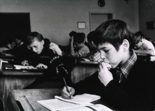 <p>Interior view of a classroom: a young boy is sitting at a desk working on an inclass assignment; he is also eating a snack.</p>