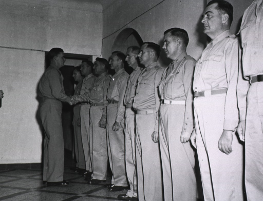 <p>The nine recipients stand in a row as Major General Hughes makes his way down the line shaking the servicemen's hands.  The rightmost award recipient, Capt. Warfield, has been partially cropped from the photograph.</p>