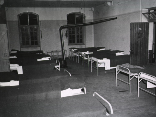 <p>View of a room furnished with two rows of single, unoccupied beds.</p>