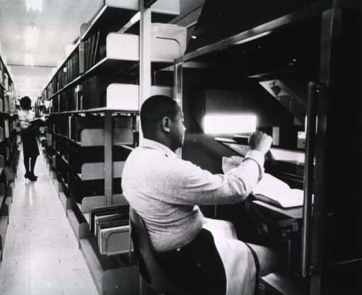 <p>Interior view: The mobile camera is at the end of the stack.  A woman is standing between the stacks holding an open book.</p>