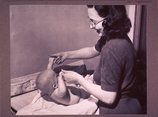 <p>An infant laying on its back clutches the fingers of a woman (standing, facing downward left) as she helps him to raise his upper torso.</p>