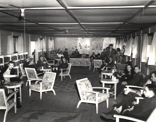 <p>Servicemen and women sit or stand in a low-ceilinged room.</p>