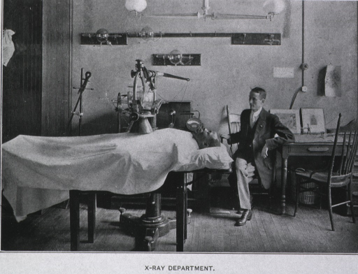 <p>An African American man is on a table covered with a sheet lying beneath an x-ray machine.  Another man, sitting above the patient's head, has his hand on a handle.</p>