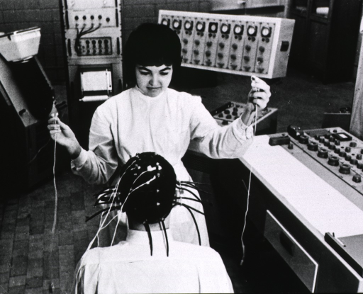 <p>Interior view: a young woman is attaching electrodes to the head of a patient sitting before her; behind them are several pieces of equipment.</p>