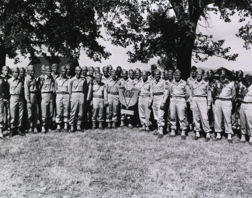 <p>A group of servicemen in several rows pose with the award beneath trees in daylight.  A couple of tents can be seen in the background.  (Cf. Awards no. 24 box 1 mil.)</p>