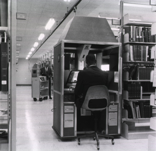 <p>Interior view: Mobile camera is in the stack area; a man is standing at a book truck.</p>