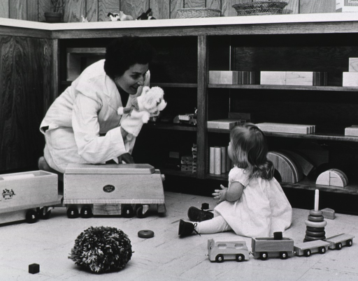 <p>A small child sits on the floor surrounded by toys; a nurse kneels nearby with a puppet on her hand.</p>