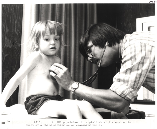 <p>Interior view of examination room: a physician holds a stethoscope to the chest of a young child sitting on a table.</p>