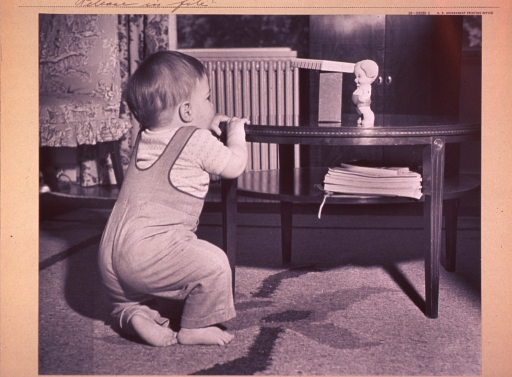 <p>An infant (full-length portrait, facing back) attempts to raise himself by grasping the edge of a coffee table upon which sits a toy.</p>