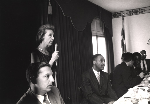 <p>An unidentified woman addresses an audience from a microphone positioned behind a table at which sits a group of men.</p>