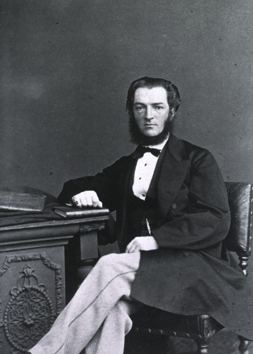 <p>Seated with right arm resting on desk; left pose.</p>