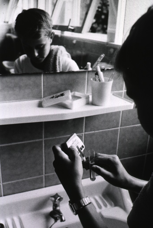 <p>Interior view of a bathroom: a young boy is using a &quot;Glukotest&quot; to check his blood sugar level.</p>
