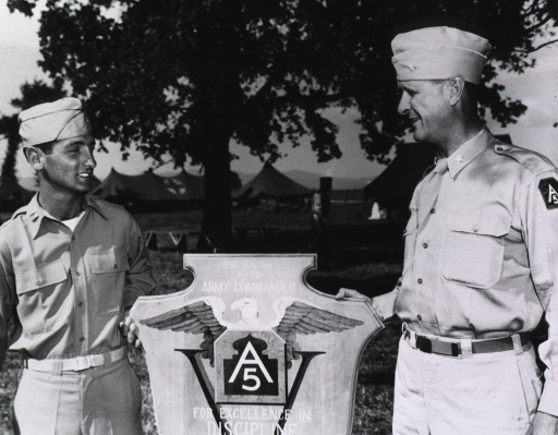 <p>The two servicemen pose with the award.  Tents can be seen in the background.  (Cf. Awards no. 23 box 1 mil.)</p>