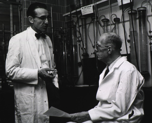 <p>Two men wearing white lab coats and glasses are in a chemical laboratory.</p>