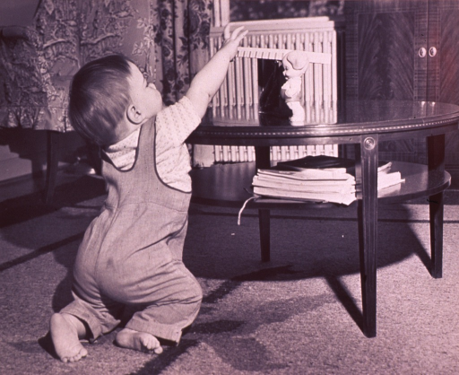 <p>Infant (full-length portrait, facing back) reaching upward toward a toy sitting on a coffee table.</p>