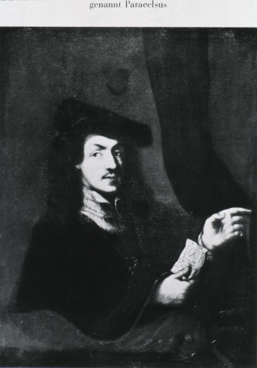 <p>Half length, seated, wearing robe and hat, showing hands.</p>