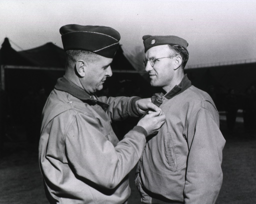 <p>Brigadier General Martin pins the medal on the jacket of Major Betts, while a group of servicemen and women stand at attention in the background.  Tents can be seen in the background.</p>