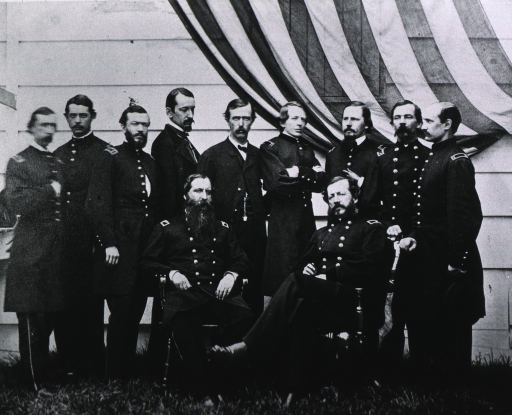 <p>Seated with the Ass't. Surgeon General, left, other staff members standing behind them.</p>
