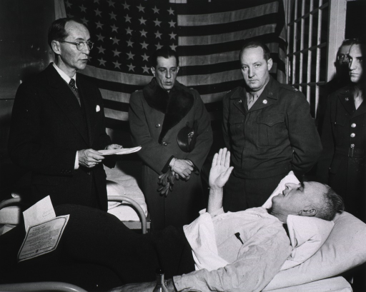 <p>Falson is supine on a hospital bed and raises his right hand.  The citation lies on the foot of the bed.  Follmer holds papers and looks down at Falson.  The other servicemen stand in a row next to the bed.  (Cf. Awards no. 27 box 1 mil.)</p>