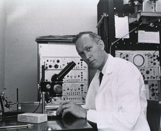 <p>Half-length, body turned to left, full face, seated wearing lab coat, in front of microscope.</p>