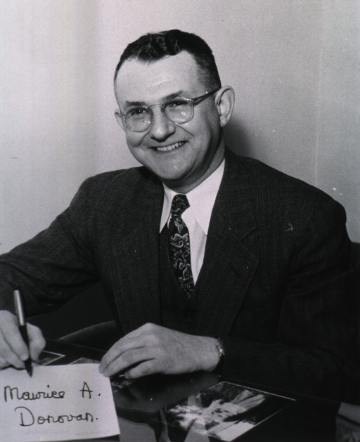 <p>Seated at desk, holding pen and a piece of paper with his name written on it.</p>